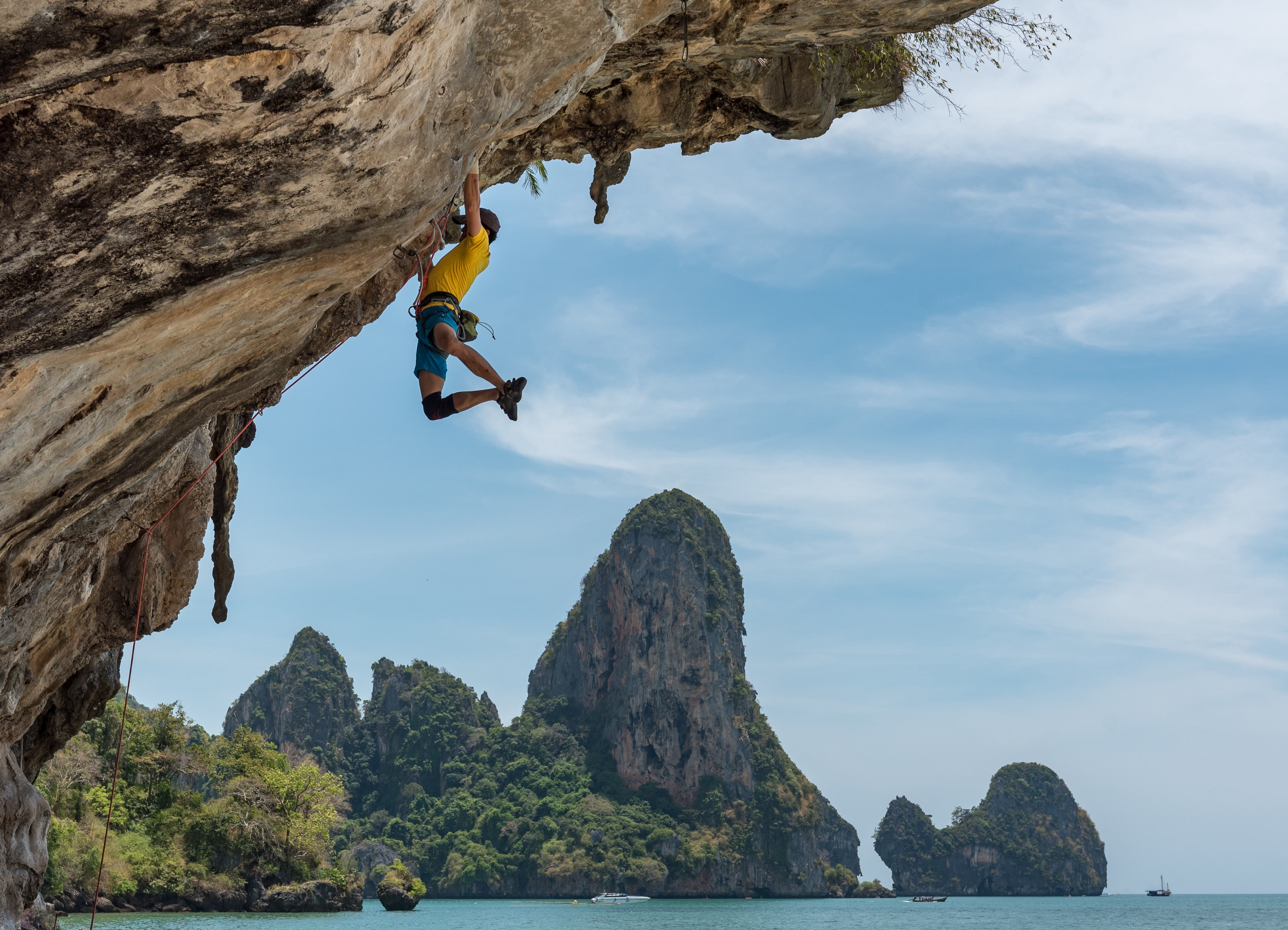 Illustrative: a man hanging from a cliff